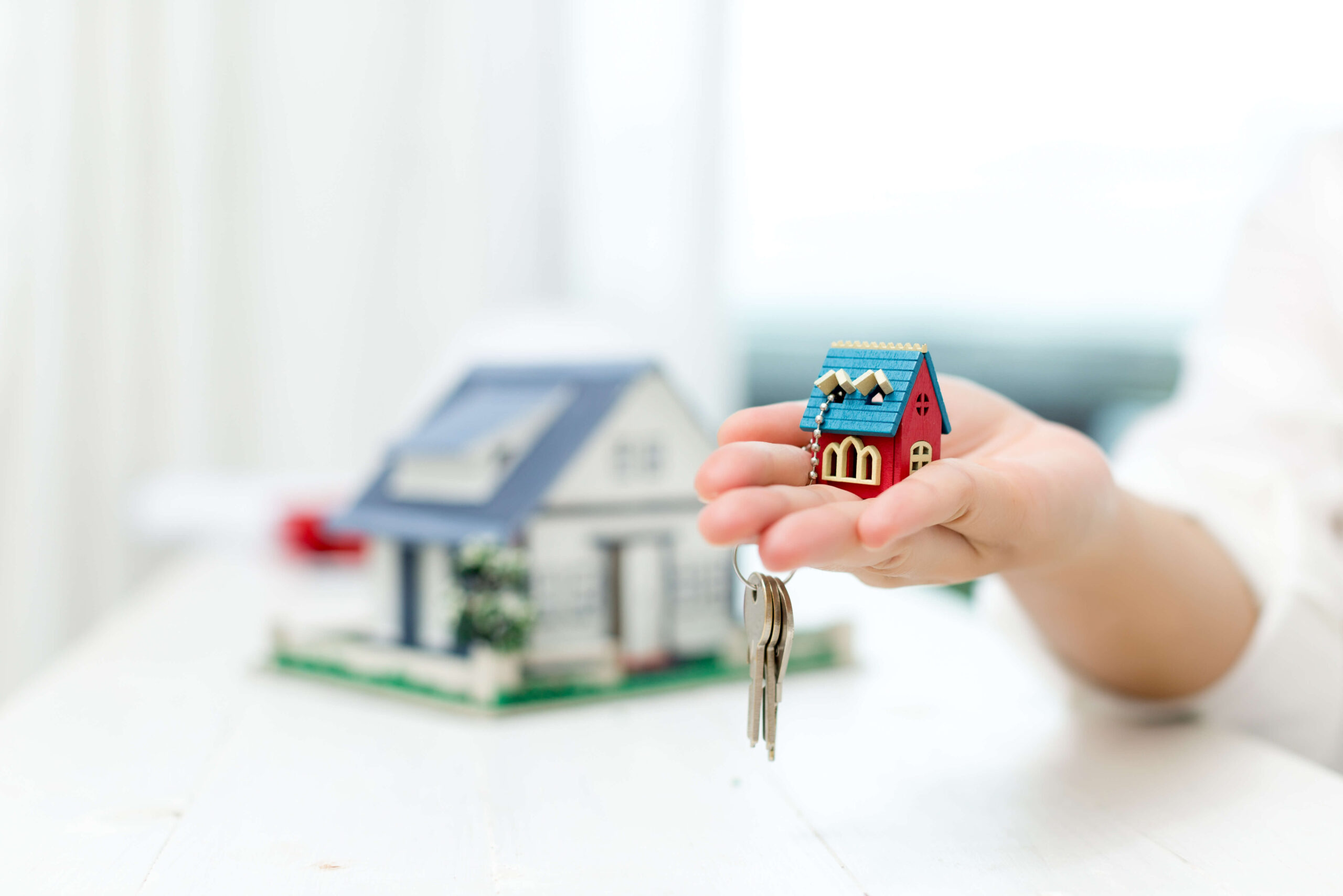 real-estate-agent-with-house-model-keys (1)